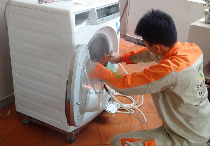 Kỹ thuật viên đang vệ sinh máy giặt