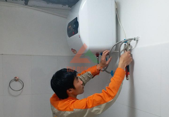 Thao tác kỹ thuật viên đang trong quá trình lắp đặt bình nóng lạnh tại nhà rất cẩn thận
